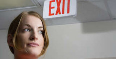 Woman Thinking by Exit Sign