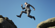 Man in Suit Jumping Across Chasm