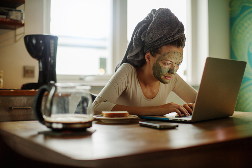 Close up of a multitasking woman using laptop in kitchen while having breakfast and wearing facial mask