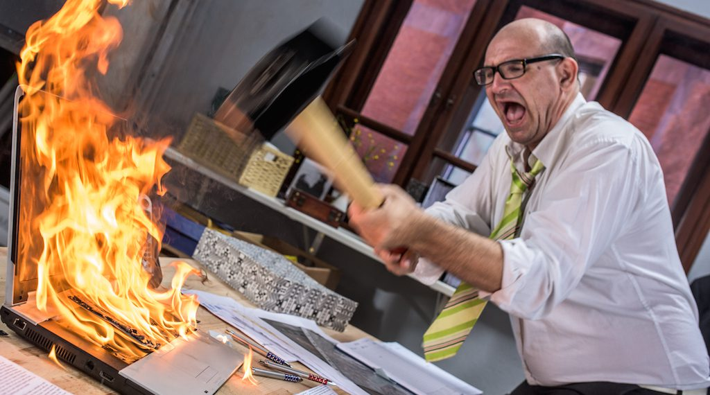 HR Manager hitting laptop on fire with hammer.