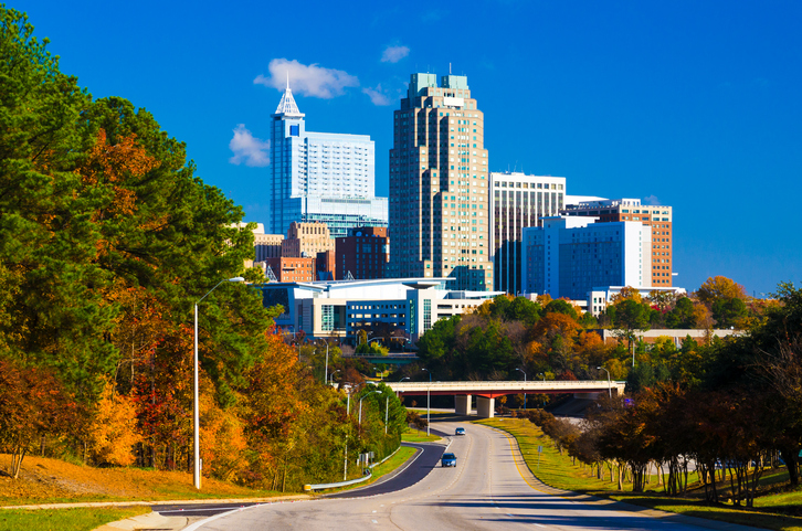 Skyline of Raleigh in the distance with a road leading to it and autumn colored trees on the left side.
